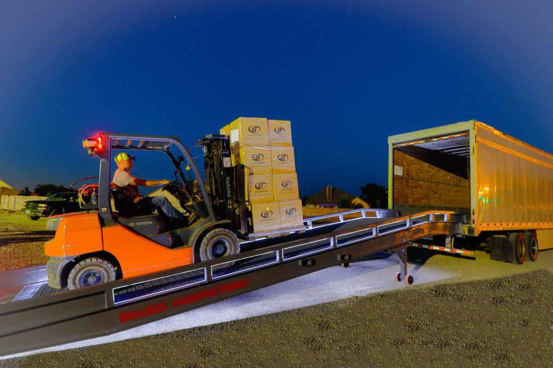 Side view of fork lift loading a pallet of Lit coolers on a truck using a Safety Lighted Ramp by Brazos