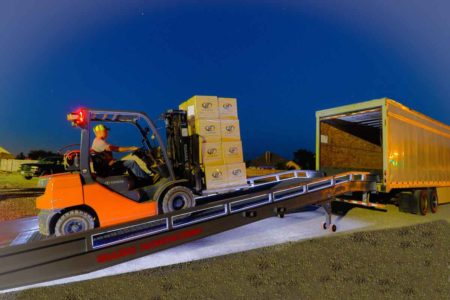 Side view of fork lift loading a pallet of Lit coolers on a truck using a Safety Lighted Ramp by Brazos-Portable Forklift Ramp